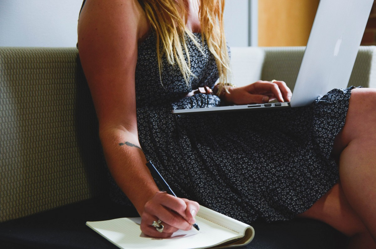 Woman using a laptop and writing