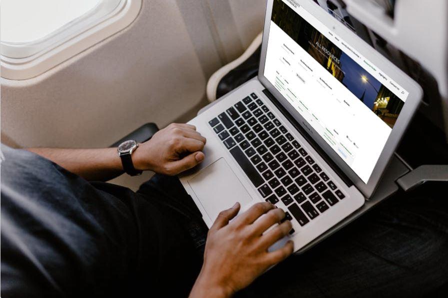 A man using a laptop on a plane